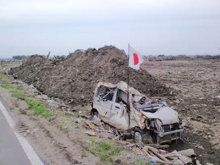 写真:津波で全てが流し去られた跡に積みあがった瓦礫の山とペチャンコになった軽自動車。その脇には日の丸の旗が力強く風になびいていた。