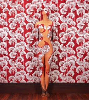 model painted to blend in with red and whie floral wallpaper