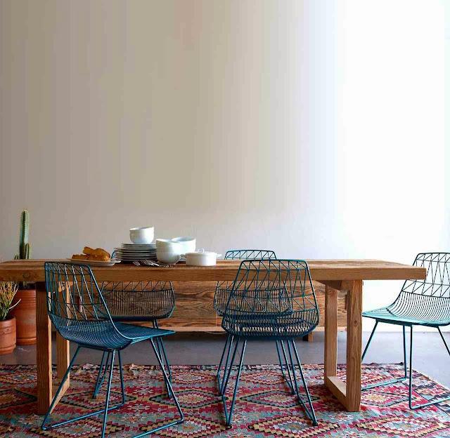 Niebieskie druciane krzesła, drewniany stół i wzorzysty dywan