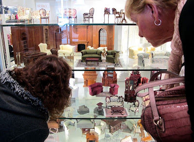 Customers browsing the displays of dolls' house miniatures at Fairy Meadow Miniatures.