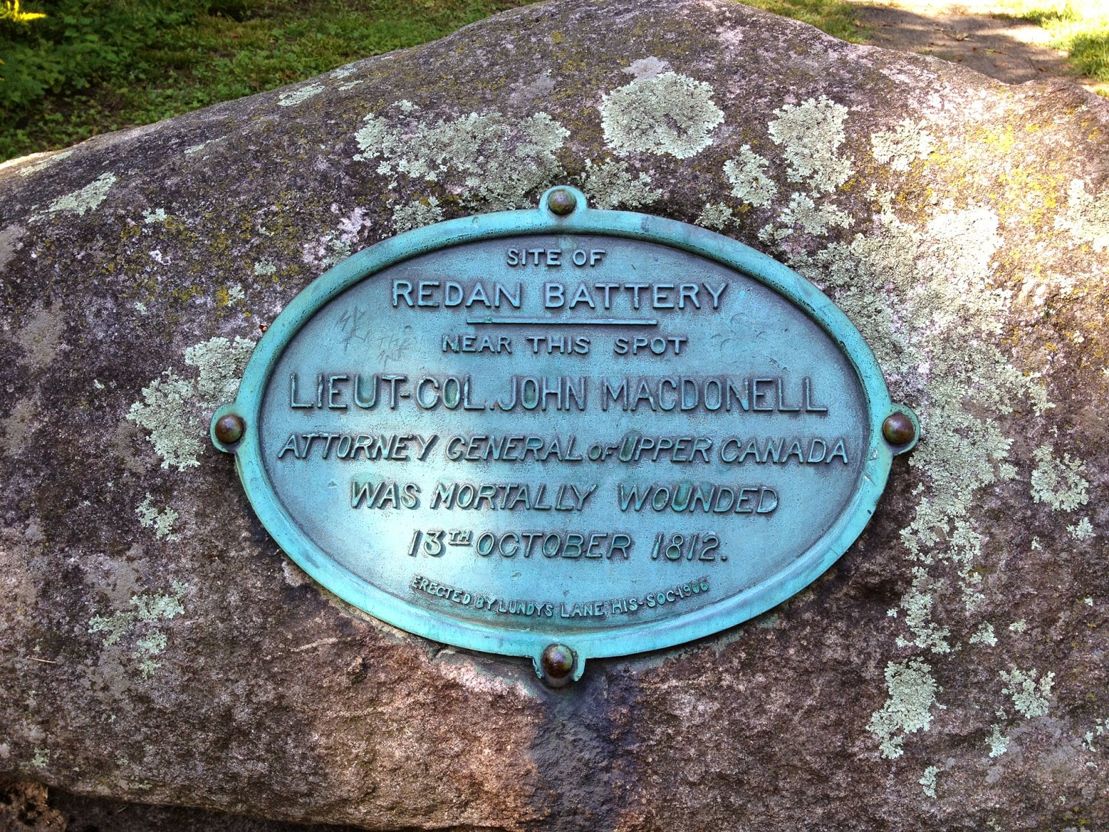 Colour photo of stone with plaque on it stating that Macdonell fell at this spot.