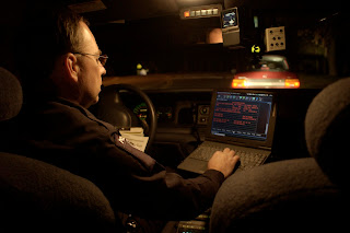 An officer in a patrol car during night duty using onboard computer.