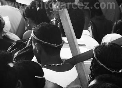 Na Via Sacra, homem carrega uma simbólica cruz e usa uma coroa de espinhos