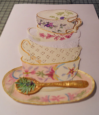 A perspective view of a handmade card that has five handmade really cute tea cups