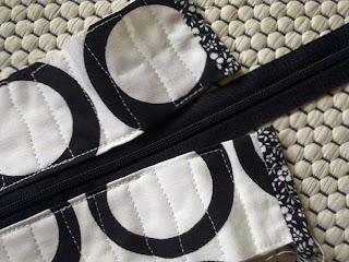 Musta-valkoinen vetoketjulipare tilkkulaukkuun - päiden päättely ennen vetoketjun kiinnittämistä kokonaan