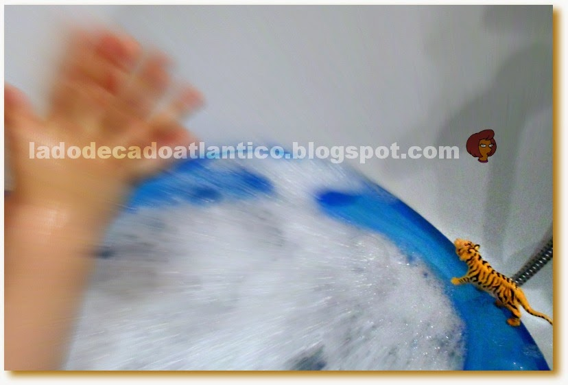 Imagem de uma banheira de criança com espuma e um tigre de brinquedo na borda.