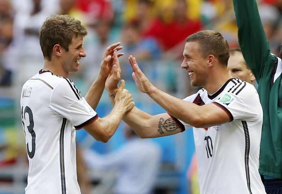 Germany's Thomas Mueller, left, is greeted by Lukas Podolski after being substituted after scoring a hat-trick during the group G World Cup soccer match between Germany and Portugal at the Arena Fonte Nova in Salvador, Brazil, Monday, June 16, 2014.