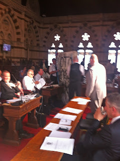 The writing-covered mattress is taken into the council chamber, where security can be seen taking it out