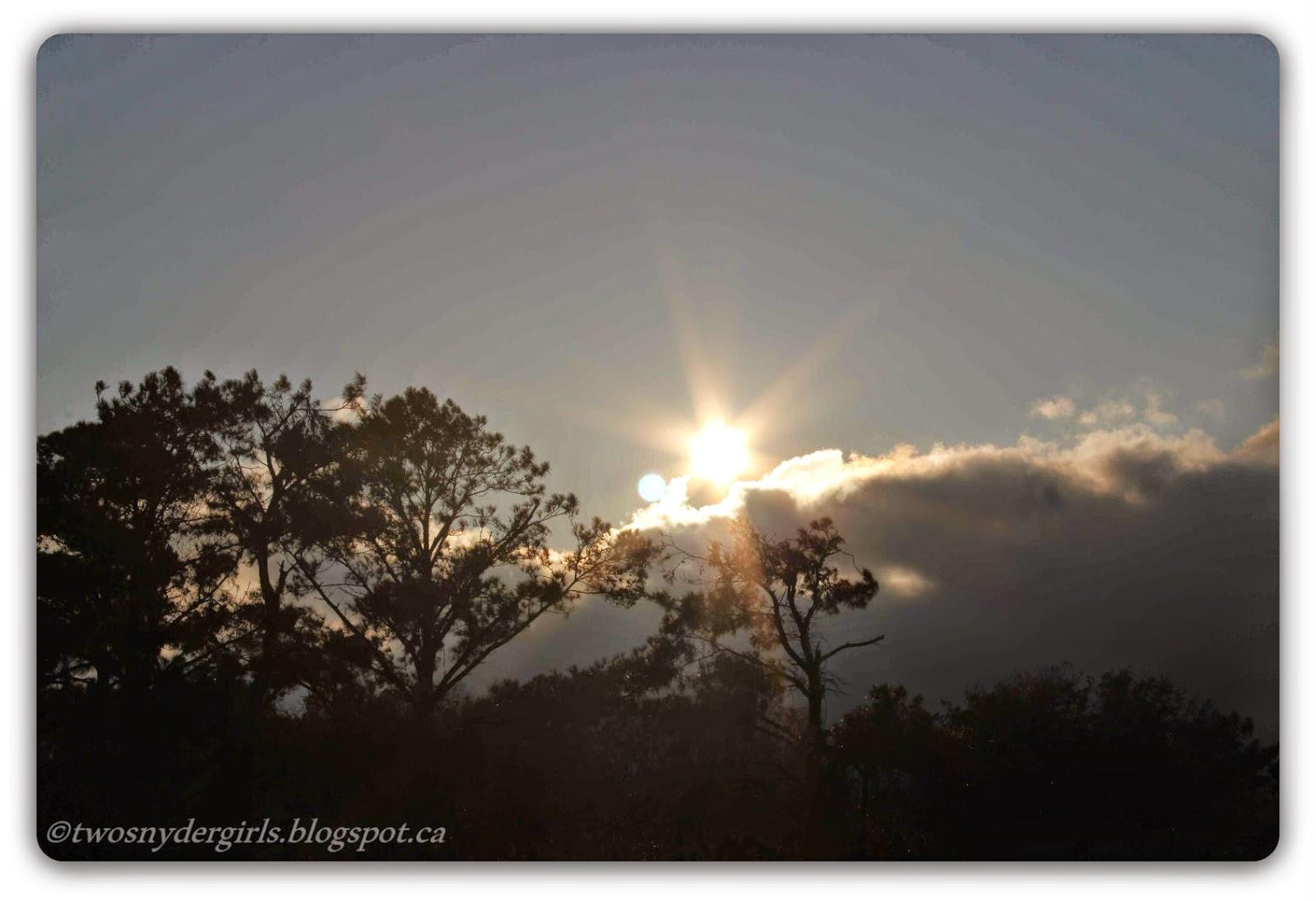 Sun rising above a cloud