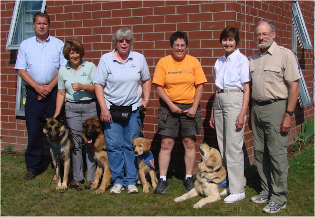 Six people are standing in front of a brick wall. From left to right are a man wearing dark blue pants and a light blue shirt, a german shephear dog, a woman wearing a light green shirt and gray pants, another german shepherd dog, a woman wearing a light gray shirt and blue jeans, a young golden retriever puppy, a woman wearing an orange shirt with dark kahki shorts, a golden retriever, a woman wearing a white shirt and light kahki pants, a man wearing a beige shirt and light green kahki pants.