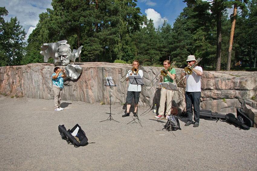 Um trio de trombones de varas a tocarem junto ao busto de Sibelius e uma mulher a tirar-lhes uma fotografia