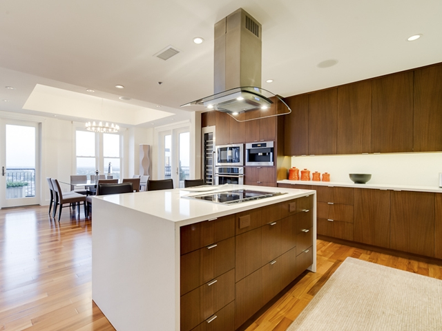 Photo of modern kitchen with wooden furniture and dinning room in the background