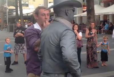 hombre estatua le pega una trompada a un acosador