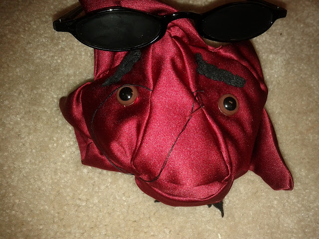 The red satin star has been filled with stuffing and awaits his sunglasses.  A silver needle with black thread sticks out of his nose waiting to sew the glasses in place.