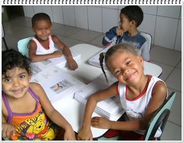 Crianças felizes com os livros do projeto Aymará