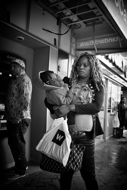 A mother and child on Adderley street Cape Town - the child is catching raindrops on her tongue.
