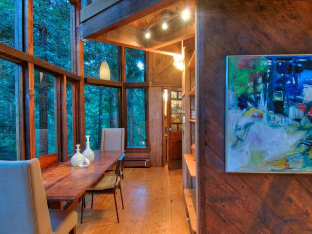 Photo of hallway and small dinning table inside of tree house in the forest