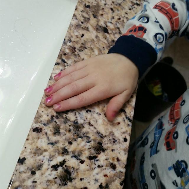 kid with pink nail polish