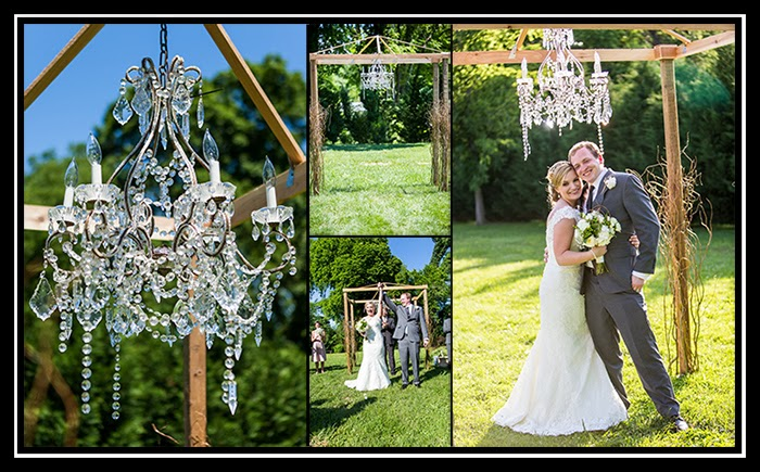arbor made for wedding with a chandelier, bride and groom posing with the arbor