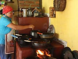 Dona Iraci e sua cozinha: fogão a lenha, leitão assado, feijão na panela de barro, farofa de milho,