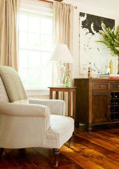 Living room in a farmhouse with an ticking stripe armchair, throw, wood floor and wooden cabinet