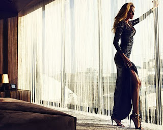 Blake Lively in an evening gown in a bedroom, shows off her leg