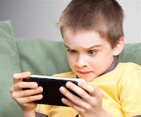 Little boy glued to his hand held video game