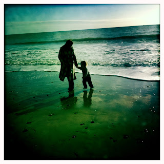 Mummy and Isaac running away from the waves on Bournemouth beach
