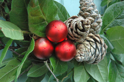 Red baubles, pine cones and birch twigs on a fresh viburnum leaf Christmas wreath.