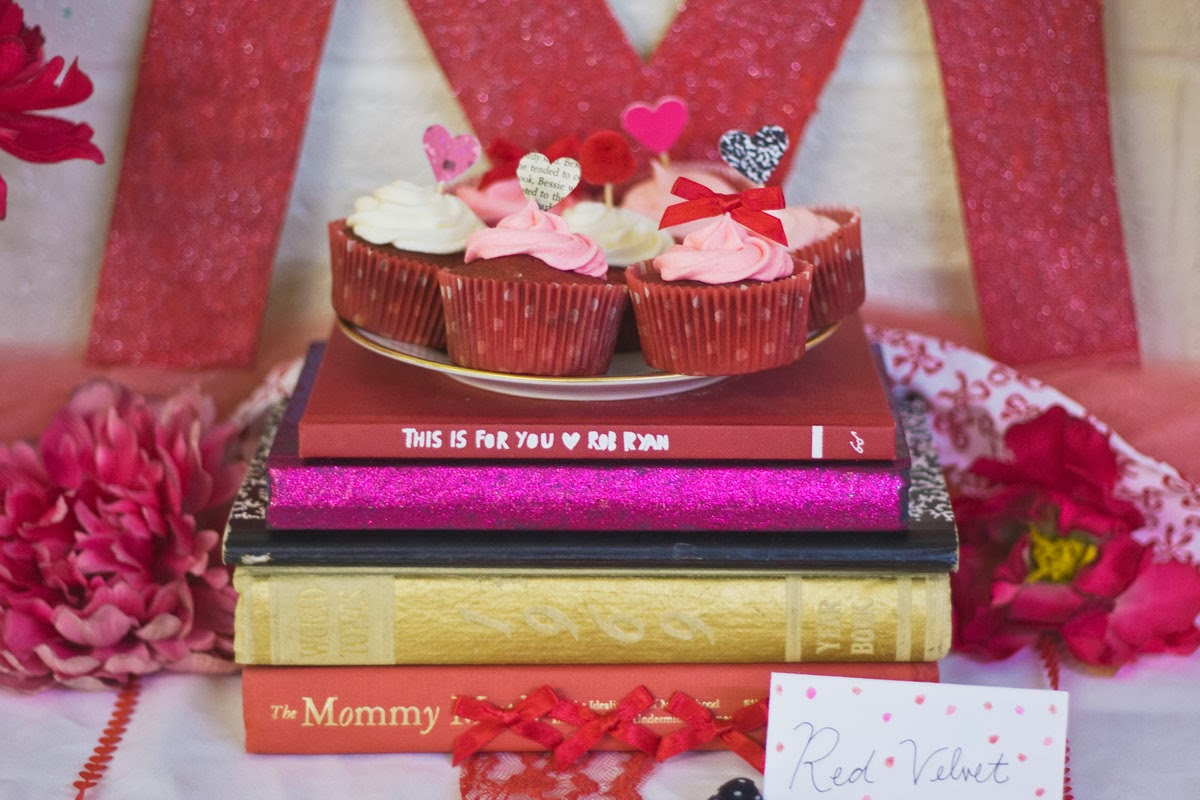 Coral, red, and pink cupcakes on book centerpiece