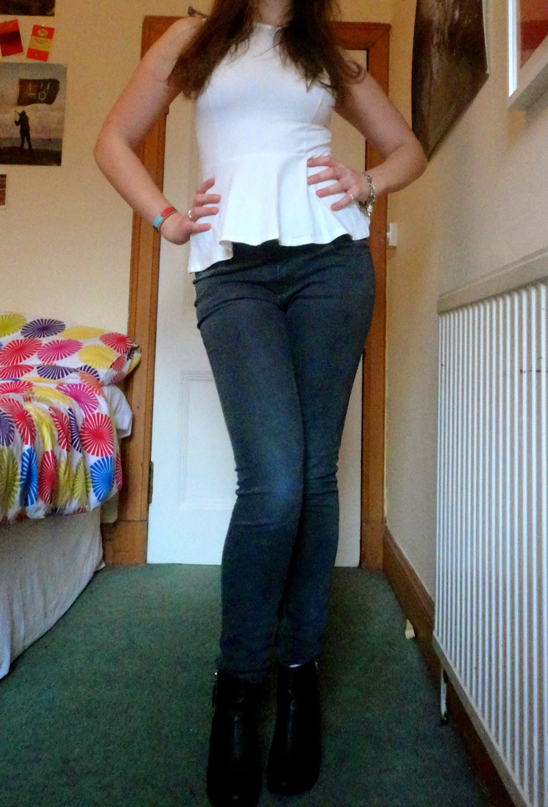 Outfit of white peplum top, grey skinny jeans & black heeled ankle boots