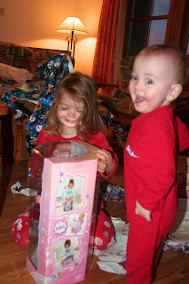 Photo of little girl opening a Christmas present and her baby brother smiling in delight