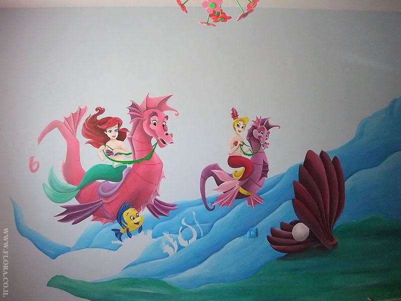 ציור קיר בתהליך עבודה. בת הים הקטנה אריאל ואחותה הרוכבות על סוסי ים. קונכייה ובתוכה פנינה. ברקע גלי ים