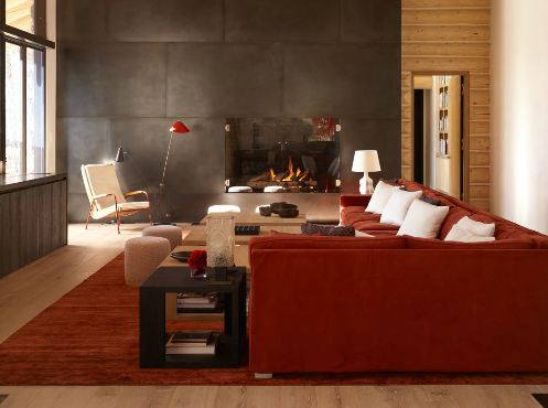 i2i jonn coolidge's rust and gray living room with burnt orange velvet sofa with white accent pillows and a modern sectional fireplace wall