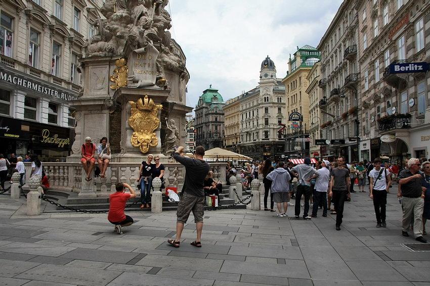 Rua pedonal com muitas pessoas em circulação e algumas a tirarem fotografias junto à coluna