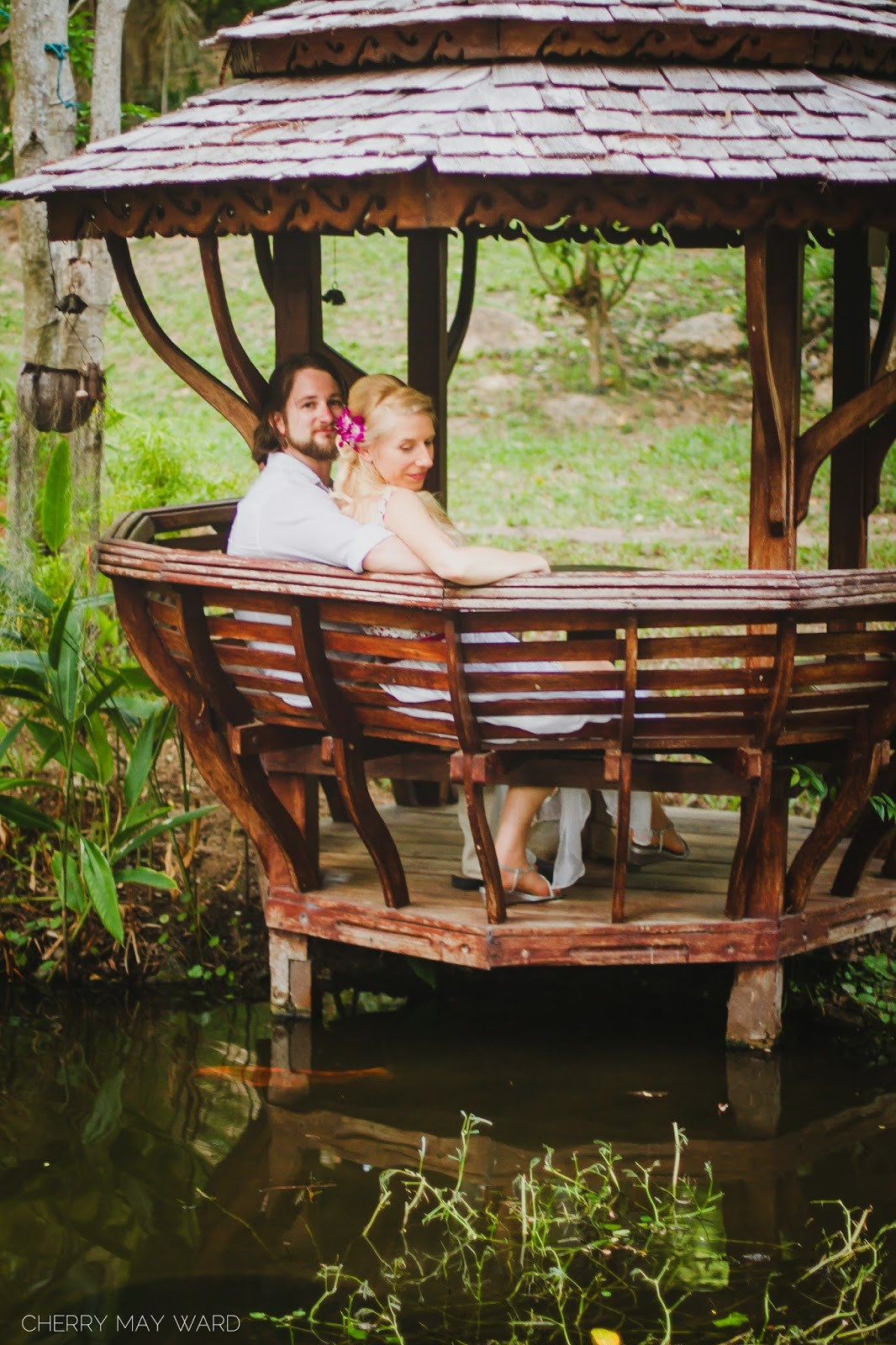 beautiful photos of bride and groom sitting in pavilion, bride and groom sitting in Thai Sala in the garden