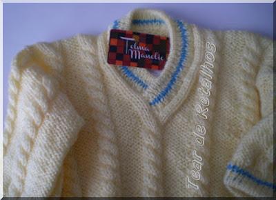 Blusa infantil branca com detalhes em azul na gola e nos punhos, feita em tricô manual com lã acrílica