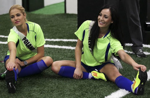 Miss New Zealand 2011 Priyani Puketapu and Miss Poland 2011 Rozalia Mancewicz stretch before they play an exhibition football match