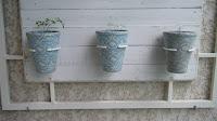Três vasos decorados com tecido encaixados em argolas