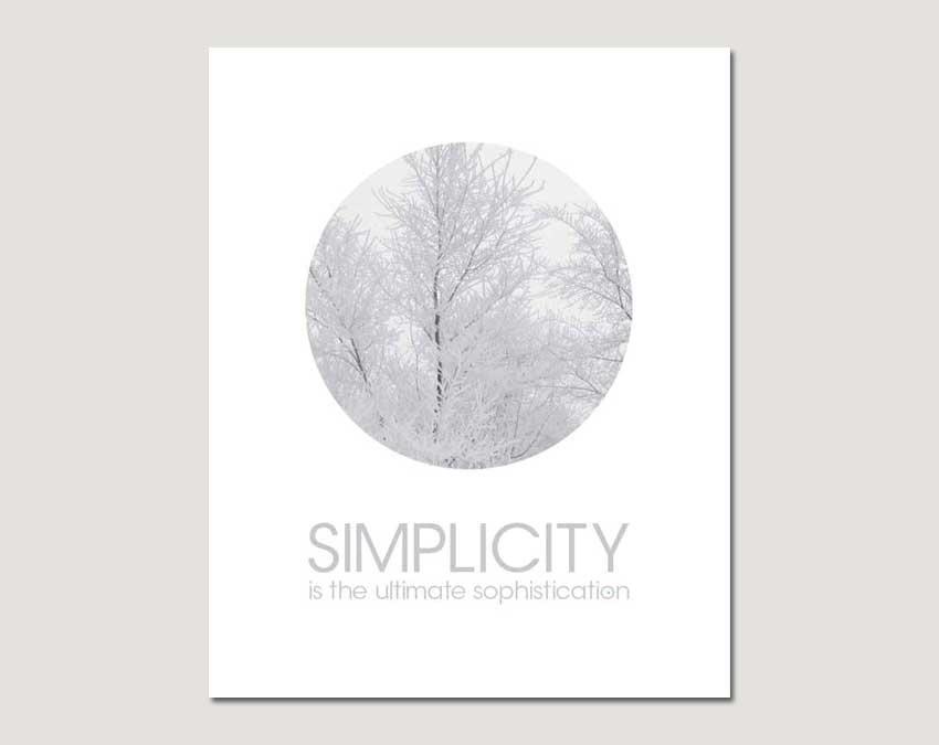 circle with frost covered trees text simplicity is the ultimate sophistication on grey