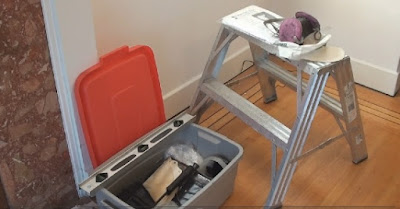 some basic interior painting tools displayed on a two step stepladder