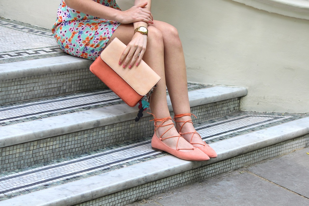 peexo fashion blogger wearing floral midi dress and pink clutch and pink lace up flats