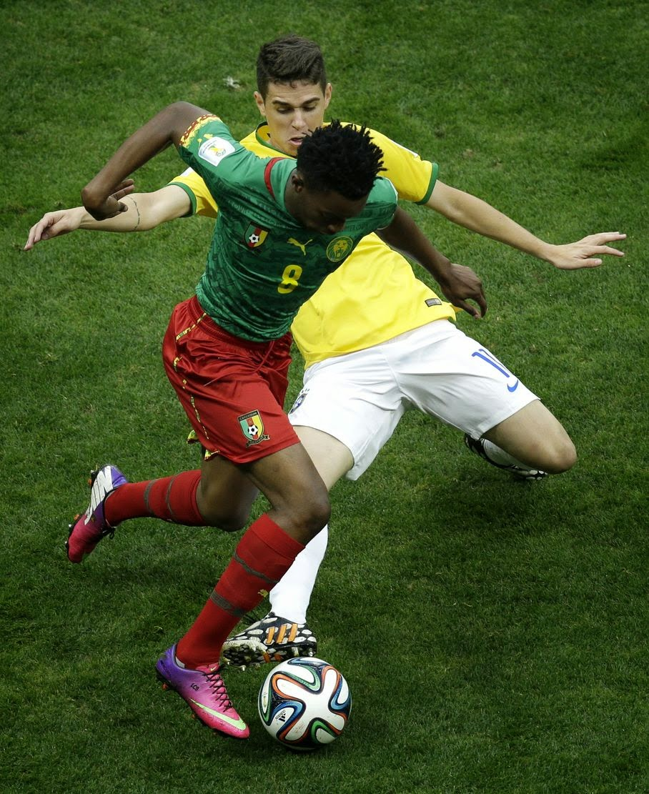 Brazil's Oscar fights for the ball with Cameroon's Benjamin Moukandjo during the group A World Cup soccer match between Cameroon and Brazil at the Estadio Nacional in Brasilia, Brazil, Monday, June 23, 2014.