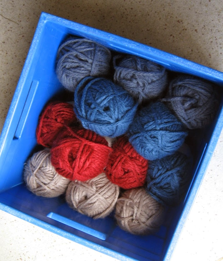 Above view of a light blue square hobby crate containing three skeins of each colour: grey, blue, red and camel.