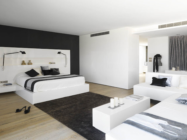 Modern white bedroom with one black wall and carpet