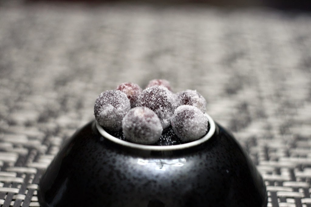 An inverted bowl displaying seven sugar frosted cranberries.