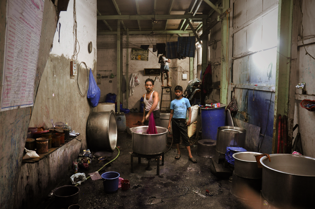 Image of men soaking and washing clothes in a factory in Dharavi.
