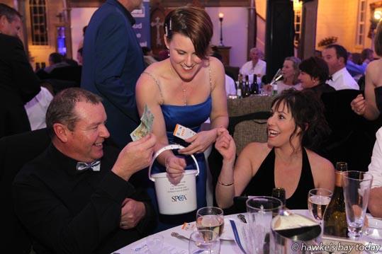 L-R: Dave Johnson, Napier, Deena Paling, volunteer, Napier SPCA, Debbie Townshend, Napier, buying shot glasses filled with ice, with a chance of finding a token for a $500 watch when the ice melts - SPCA and Harcourts Glamourpuss Ball and Charity Auction, fundraising event for Hastings SPCA and Napier SPCA, at The Old Church, Meeanee, Napier. photograph