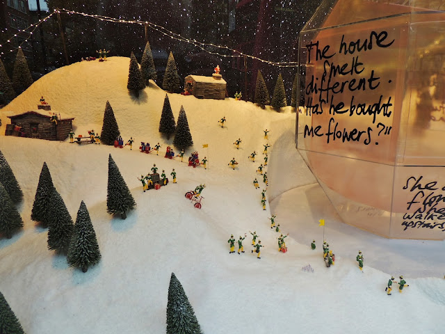 Tiny figures around a bottle in the Christmas windows of Selfridges