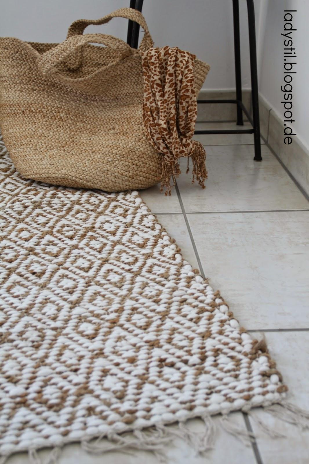 Großaufnahme eines beige weiß gemusterten Teppichs mit Basttasche
